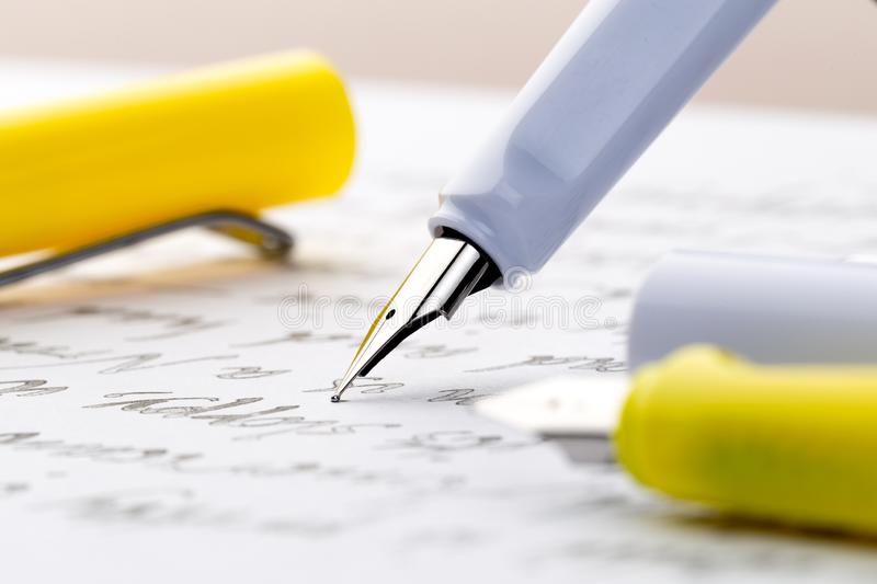 Yellow and white fountain pens on a letter.  royalty free stock images