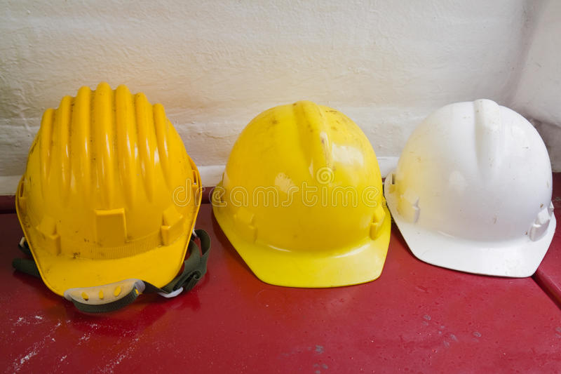 Yellow and white hard hats stock images