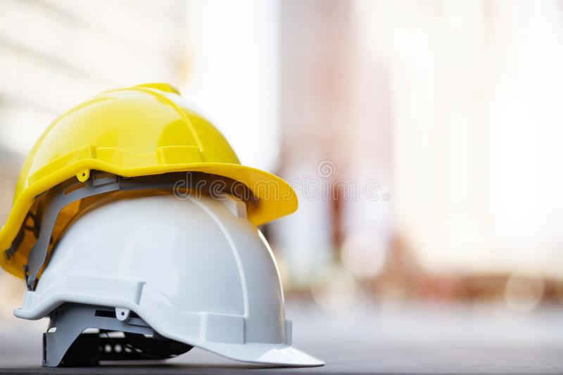 Yellow and white hard safety wear helmet hat in the project at construction site building on concrete floor on city with sunlight. Helmet for workman as royalty free stock image