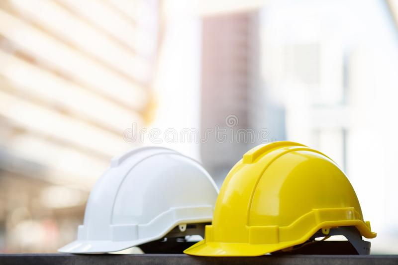 Yellow and white hard safety wear helmet hat in the project at construction site building on concrete floor on city with sunlight. Helmet for workman as stock photos
