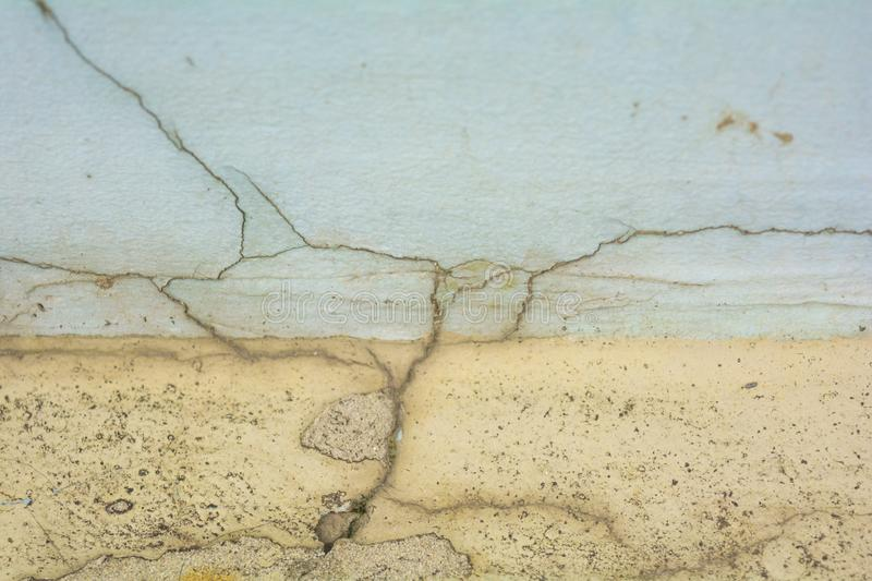 Yellow and white rough concrete wall with cracks royalty free stock photo