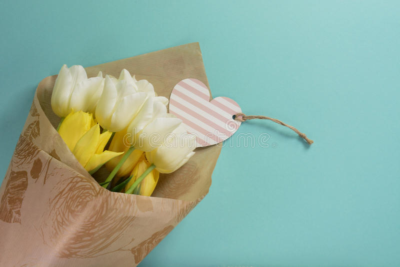 Yellow and white tulips with heart card in wrapping paper on a light turquoise background. Beautiful yellow and white tulips with heart card in wrapping paper on stock image