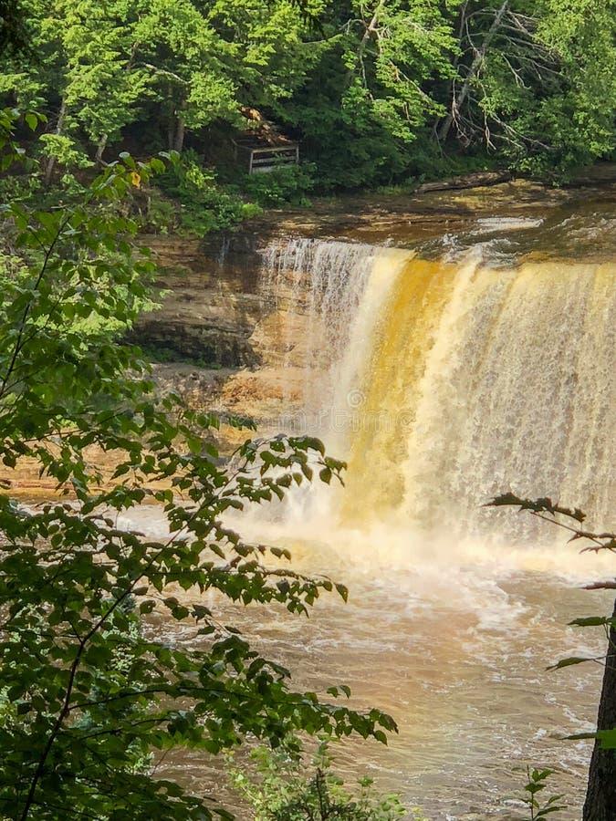 Yellow and white waterfall cascading down rocks stock photo
