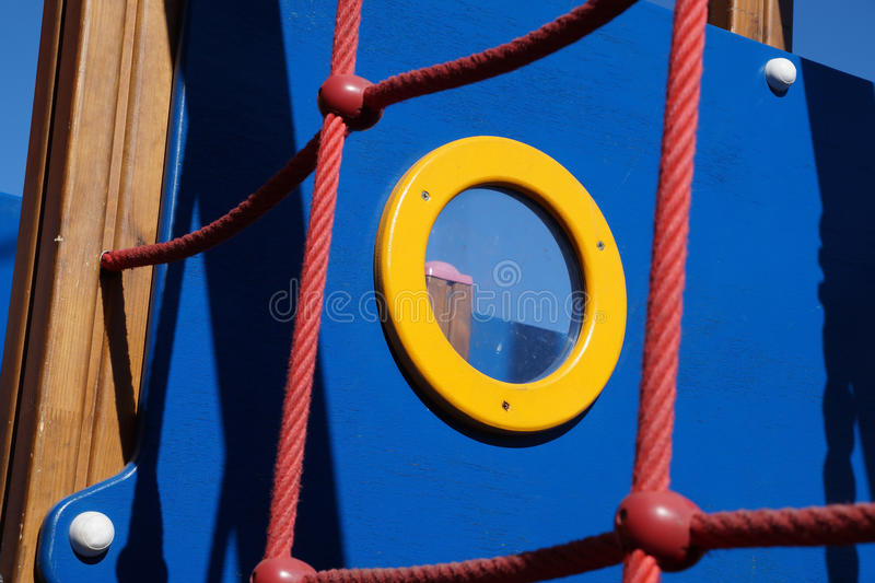 Yellow window. Window at the playground stylized under the ship stock photo