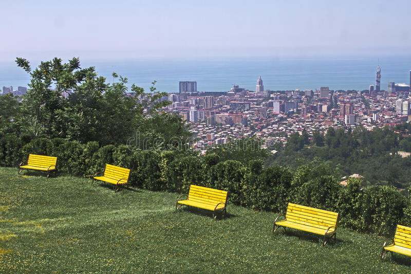 Yellow wooden benches on a green grass lawn among trees on the background of the city of Batumi, the black sea and blue clear sky. Yellow bright wooden benches stock images