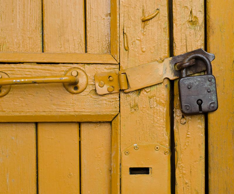 Yellow wooden door. Old padlock royalty free stock photography