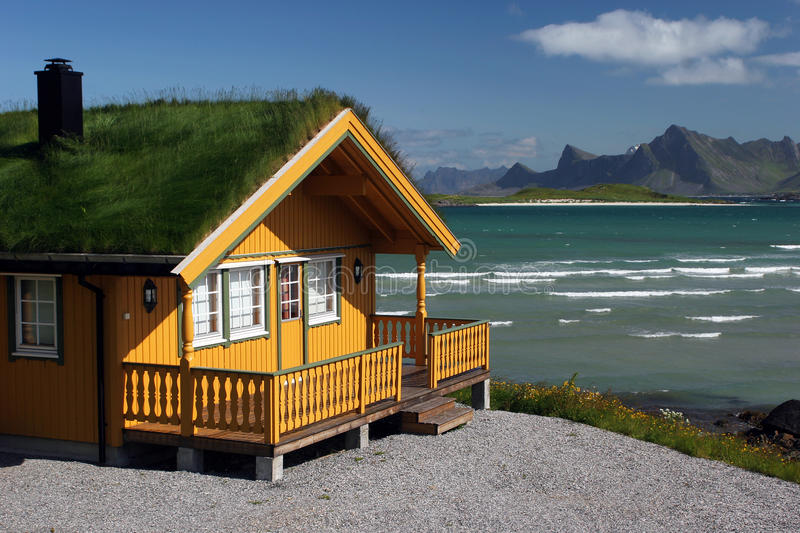 Yellow wooden house with grass roof stock images