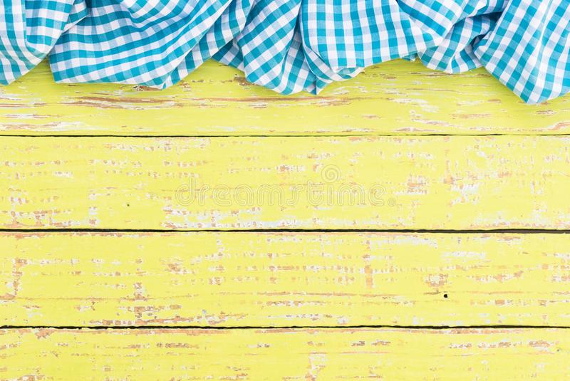 Crinkly blue tablecloth on old wooden table surface with copy space. Yellow wooden table background rustic texture, with blue checkered tablecloth, high angel royalty free stock images