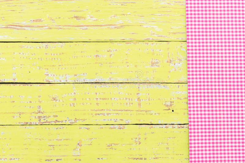 Rustic checked tablecloth on old wooden table, top view. Yellow wooden table background rustic texture, with pink checkered tablecloth, high angel view royalty free stock photo