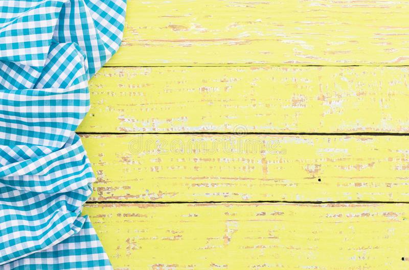 Crinkly blue checked tablecloth above old wooden table background, top view stock image
