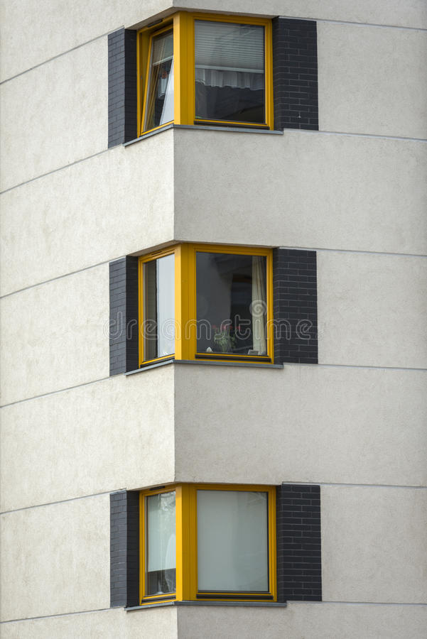 Yellow wooden windows in multi family house royalty free stock images