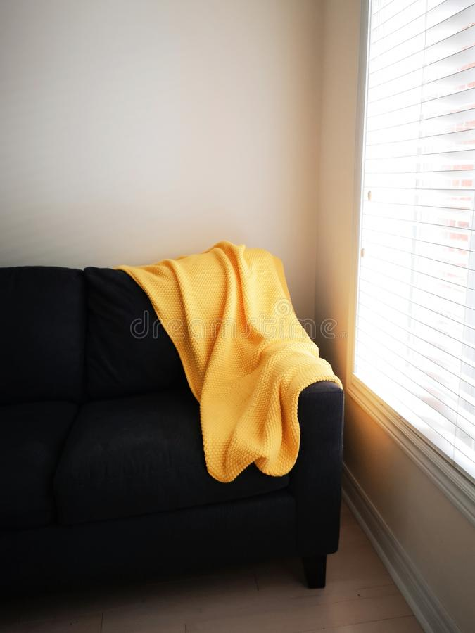 Yellow wool blanket on sofa couch. Bright yellow knitted blanket lying on dark black brown sofa couch near window with natural day light through blinds, lay royalty free stock image