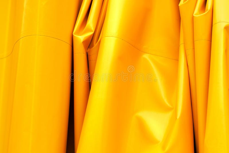 Yellow wrinkled tarpaulin background. Artificial tarp material texture royalty free stock photography