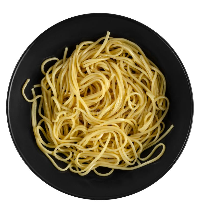 Yellow yakisoba noodles in black matte plate isolated on a white background, top view stock photography