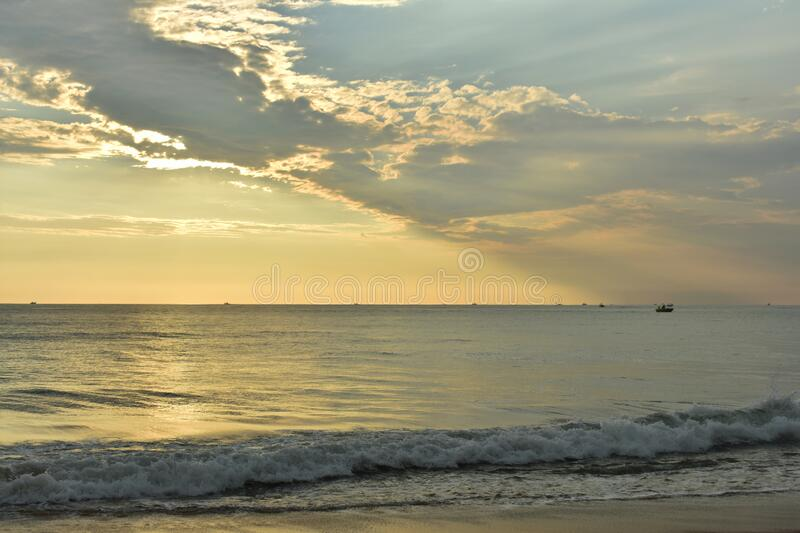 Yellowish clouds and a ocean during the beautiful sunset. India stock image
