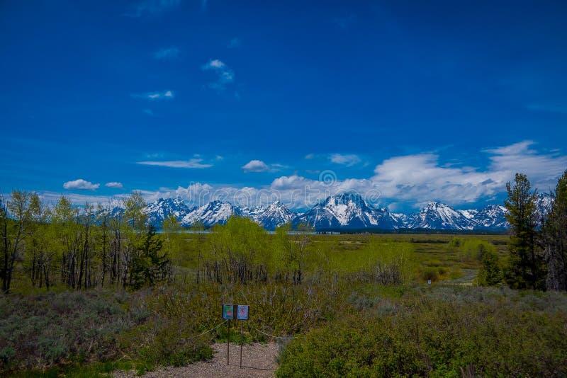 YELLOWSTONE, MONTANA, usa MAY 24, 2018: Zamyka up pouczający znak Teton pasmo i dolinny góra krajobraz zdjęcia royalty free