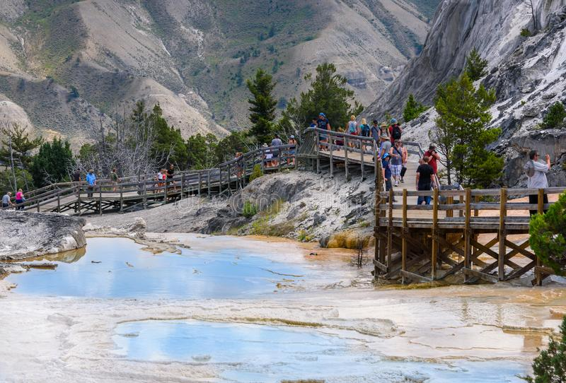 YELLOWSTONE NATIONAL PARK, WYOMING, USA - JULY 17, 2017: Mammoth hot springs pools with boardwalk, walkway. Tourists, people walki stock image