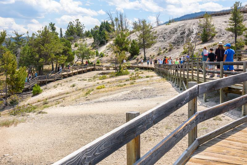 YELLOWSTONE NATIONAL PARK, WYOMING, USA - JULY 17, 2017: Tourists on boardwalk at Mammoth Hot Springs Terraces. Yellowstone Park, stock photos