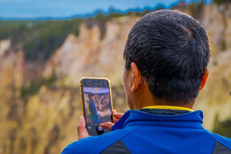 YELLOWSTONE NATIONALPARK, WYOMING, USA - 7. JUNI 2018: Schließen Sie oben vom selektiven Fokus des Mannes, der ein Mobiltelefon v lizenzfreie stockbilder