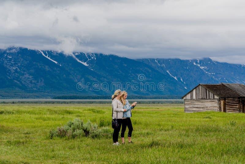 YELLOWSTONE NATIONALPARK, WYOMING, USA - JUNI 17, 2018: Turister nära huset på Moulton ladugårdar på ett präriegräsfält arkivbild