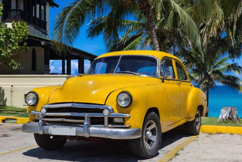 Yellwow Amerikaanse die Oldtimer onder palmen dichtbij het strand in Varadero Cuba - de Rapportage van Serie wordt geparkeerd Kub royalty-vrije stock fotografie