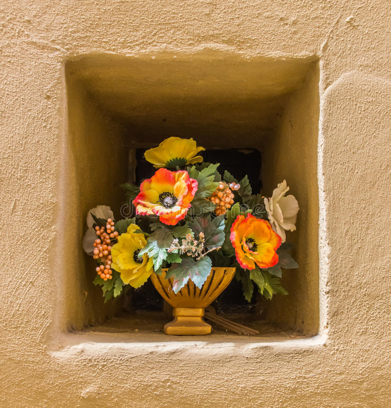 Yeloow wall niche with a pot of flowers. In Italy royalty free stock images