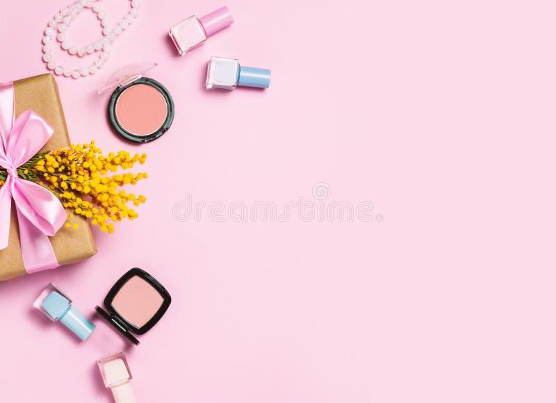 Yelow-Frühlingsblume, Geschenkbox und irgendeine Kosmetik auf rosa Frühlingshintergrund stockbild