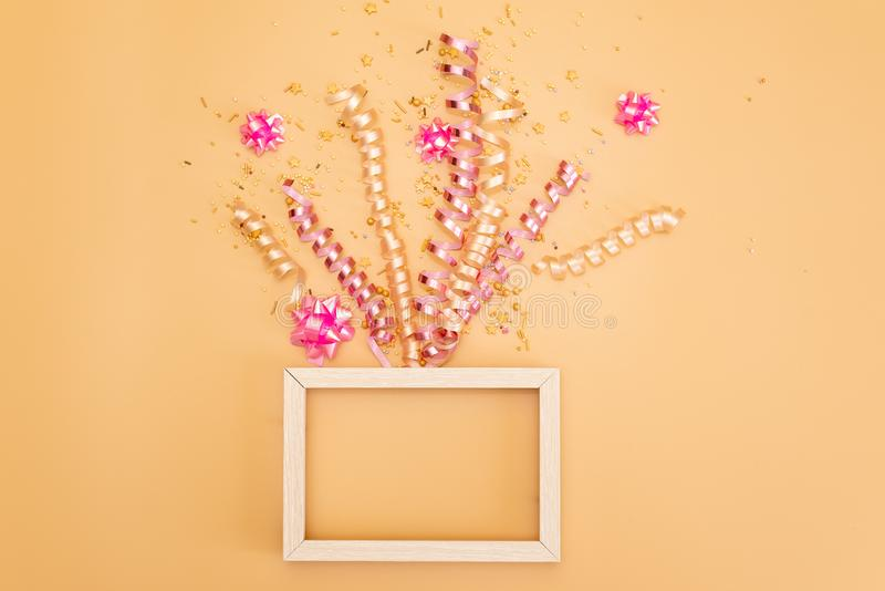 gift box with various party confetti, streamers, noisemakers and decoration on a orange background. Colorful celebration royalty free stock photo