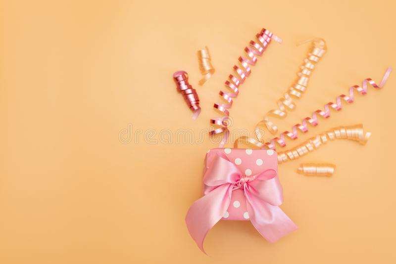 Yellow gift box with various party confetti, streamers, noisemakers and decoration on a orange background. Colorful celebration stock photo