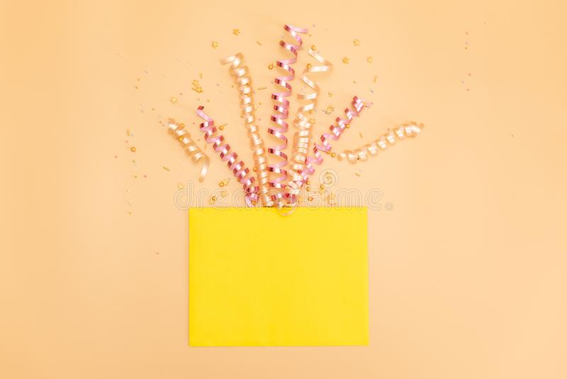 Yellow gift box with various party confetti, streamers, noisemakers and decoration on a orange background. Colorful celebration royalty free stock photos