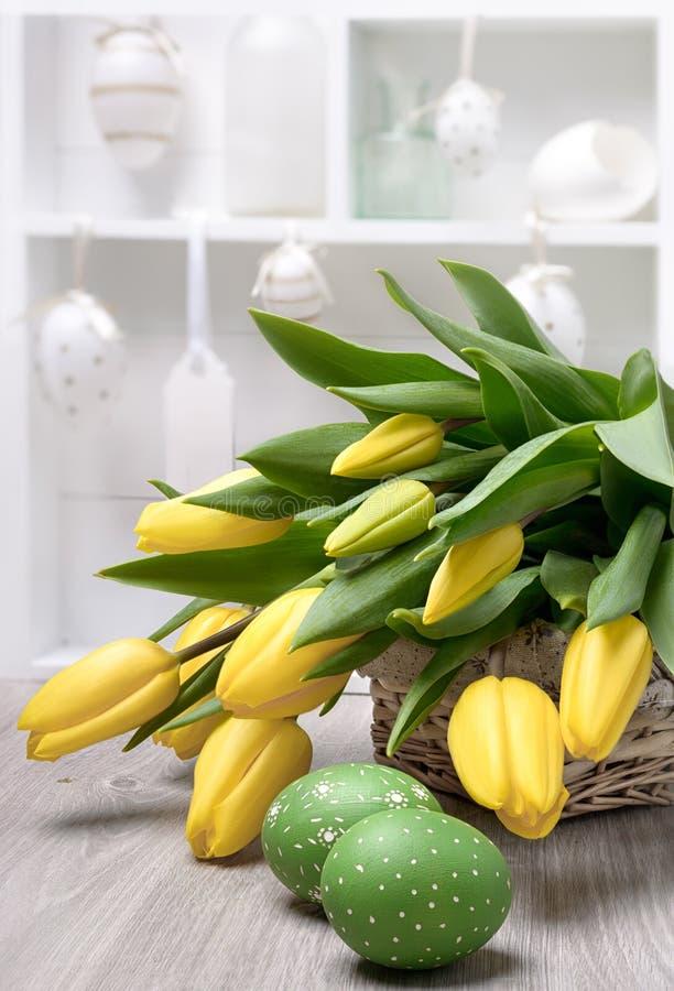 Yelow tulipany, Wielkanocni jajka i dekoracje w shadowcase, fotografia stock