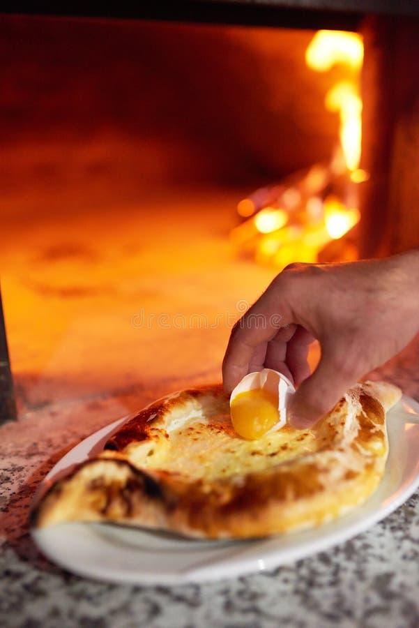 Yema de huevo del cocinero de Lozhit en el khachapuri de Ajarian preparación imagen de archivo