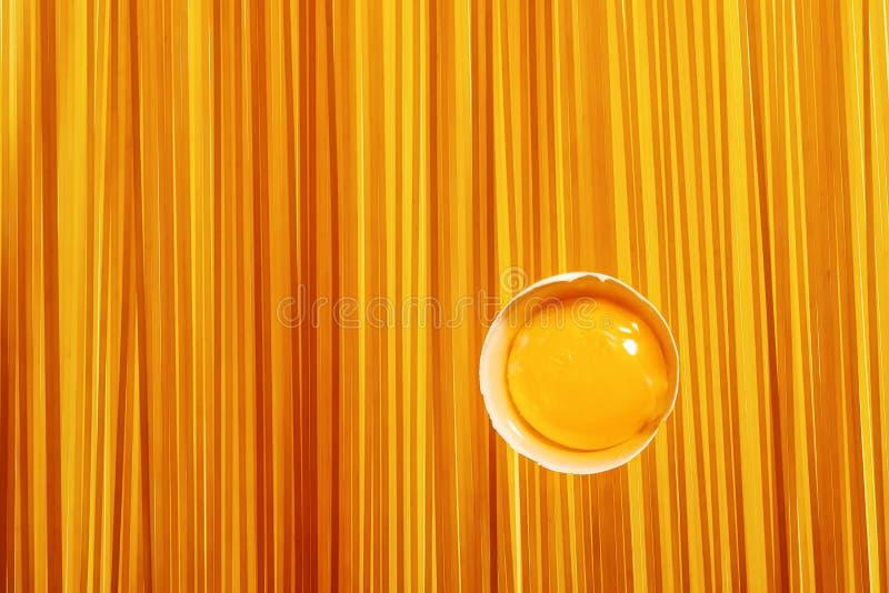 Yema de huevo en cáscara de huevo blanco en fondo de los espaguetis foto de archivo