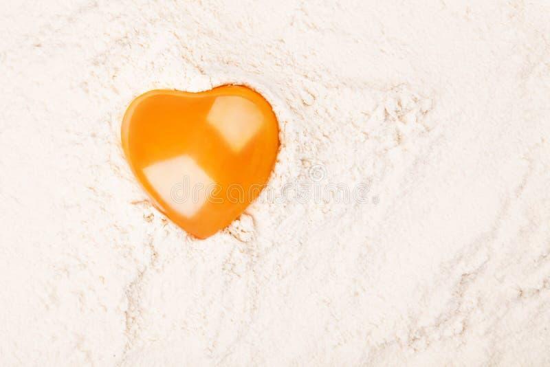 Yema de huevo en forma de corazón en la harina imágenes de archivo libres de regalías