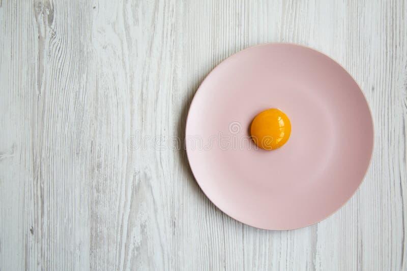 Yema de huevo en una placa rosada en un fondo de madera blanco, visión superior imagenes de archivo