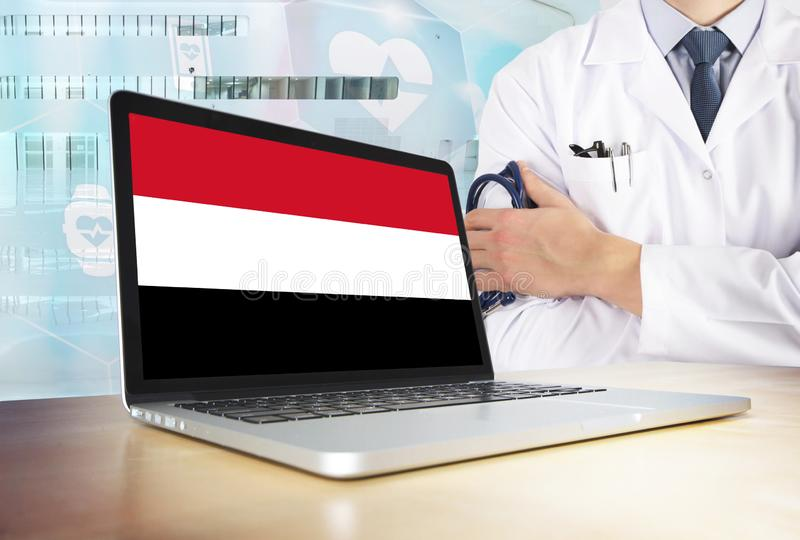 Yemen healthcare system in tech theme. Yemeni flag on computer screen. Doctor standing with stethoscope in hospital. stock images