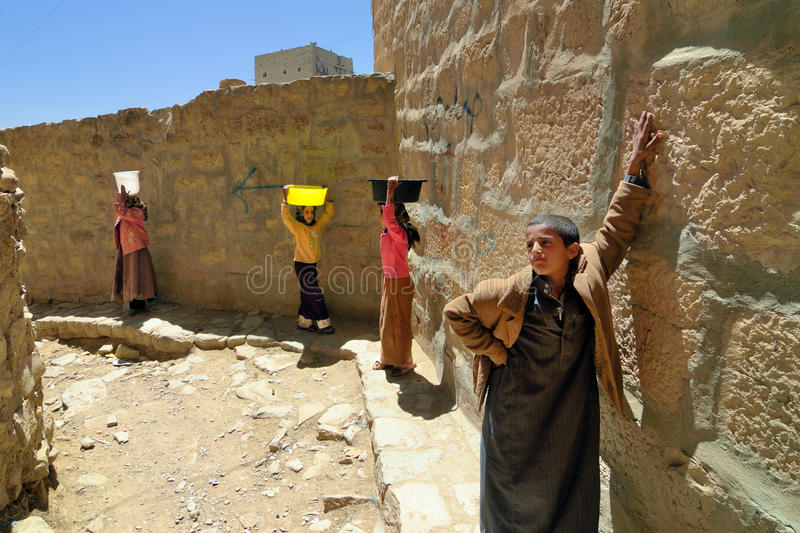 Yemeni children. HABBABAH, YEMEN - MARCH 13, 2010: Unidentified girls carry water under boy's management. From an early age children in the poorest countries in royalty free stock image