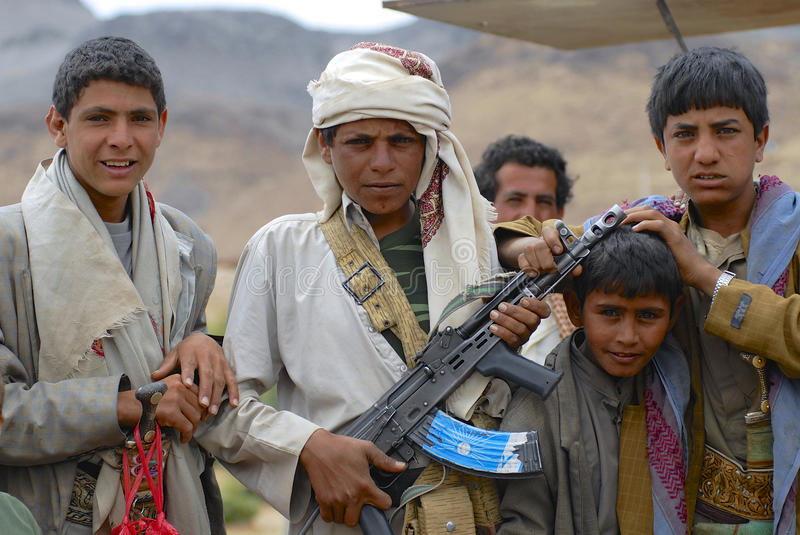 Yemeni teenagers in traditional dresses pose with Kalashnikov machine gun, Hadramaut valley, Yemen. stock image