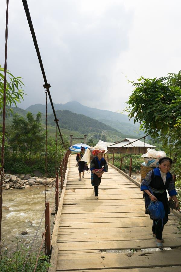 Yen Bai, Vietnam - 18 de septiembre de 2016: Gente de la minoría étnica de Hmong del vietnamita que camina en el puente de cadena fotos de archivo libres de regalías