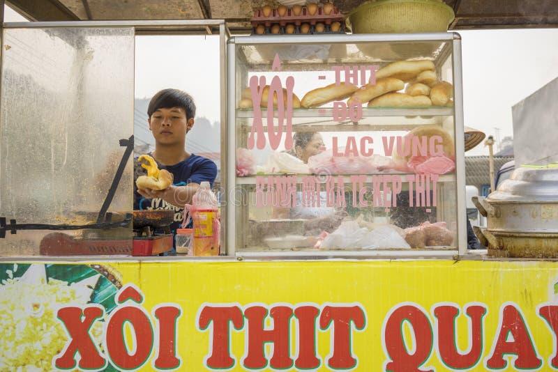 Yen Bai, Vietname - 12 de abril de 2014: O vendedor não identificado vende o pão com carne pelo carro móvel em Yen Bai, Vietname fotografia de stock