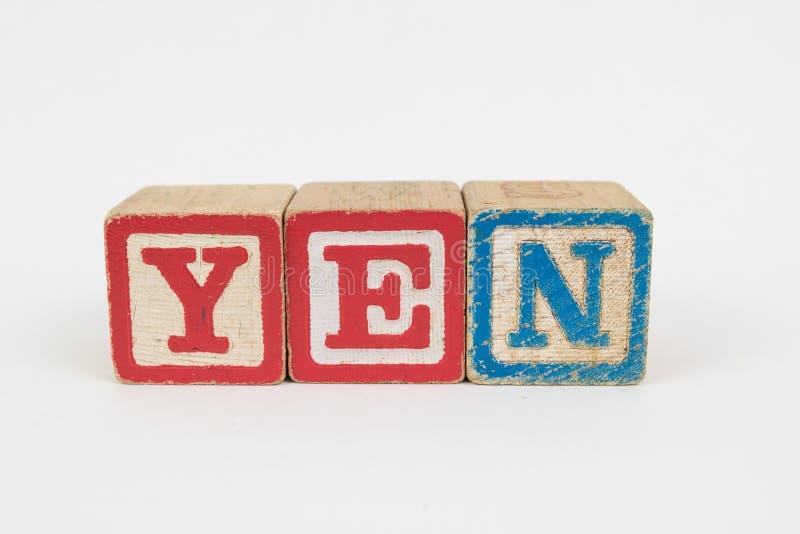 Yen di parola in blocchetti dei bambini di legno immagini stock