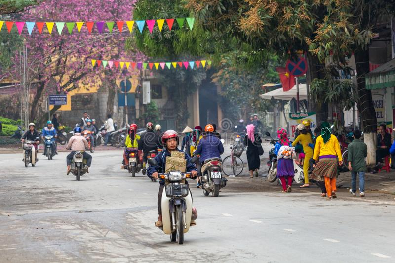 Yen Minh sunday meeting Vietnam. Ha Giang, Vietnam - March 17, 2018: Motorbike traffic at sunrise in Yen Minh with people coming from remote villages to the royalty free stock image