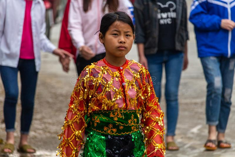 Yen Minh sunday meeting Vietnam. Ha Giang, Vietnam - March 17, 2018: Well dressed woman from Hmong ethnic minority walking from their villages to the sunday royalty free stock photography