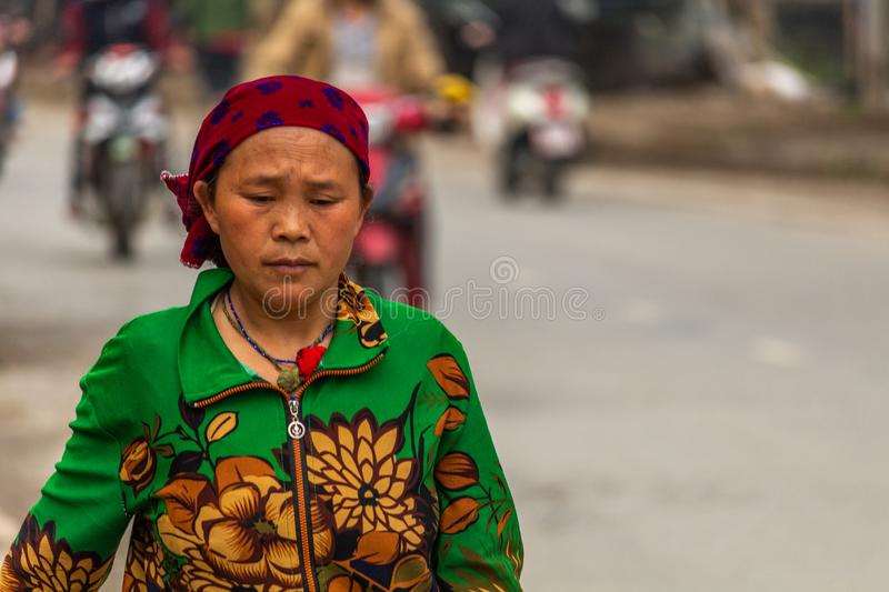 Yen Minh sunday meeting Vietnam. Ha Giang, Vietnam - March 17, 2018: Well dressed woman from Hmong ethnic minority walking from their villages to the sunday stock images