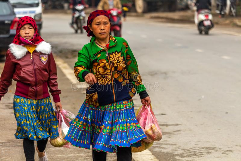 Yen Minh sunday meeting Vietnam. Ha Giang, Vietnam - March 17, 2018: Well dressed women from Hmong ethnic minority walking from their villages to the sunday stock photo