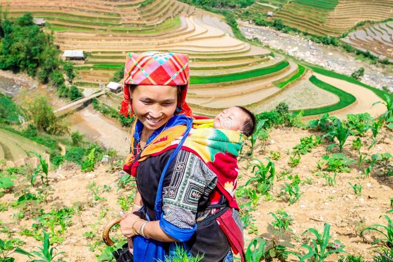 YENBAI, VIETNAM - MEI 16, 2014 - Etnisch mamma en haar kind die gaan werken royalty-vrije stock afbeelding