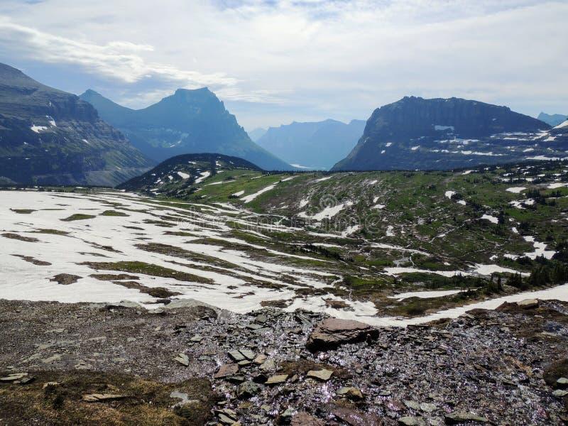 Yendo al camino de Sun, vista del paisaje, campos de nieve en Parque Nacional Glacier alrededor de Logan Pass, lago ocultado, ras foto de archivo libre de regalías
