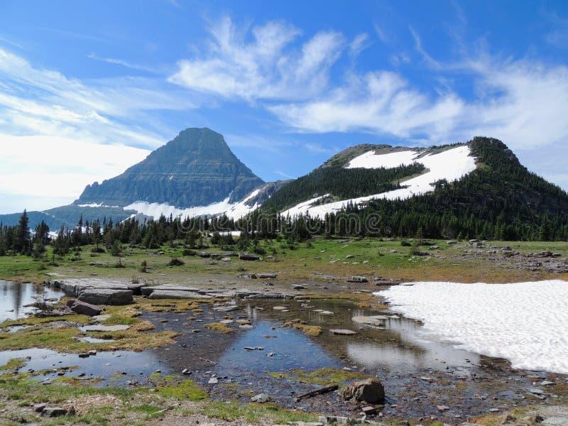 Yendo al camino de Sun, vista del paisaje, campos de nieve en Parque Nacional Glacier alrededor de Logan Pass, lago ocultado, ras fotos de archivo libres de regalías
