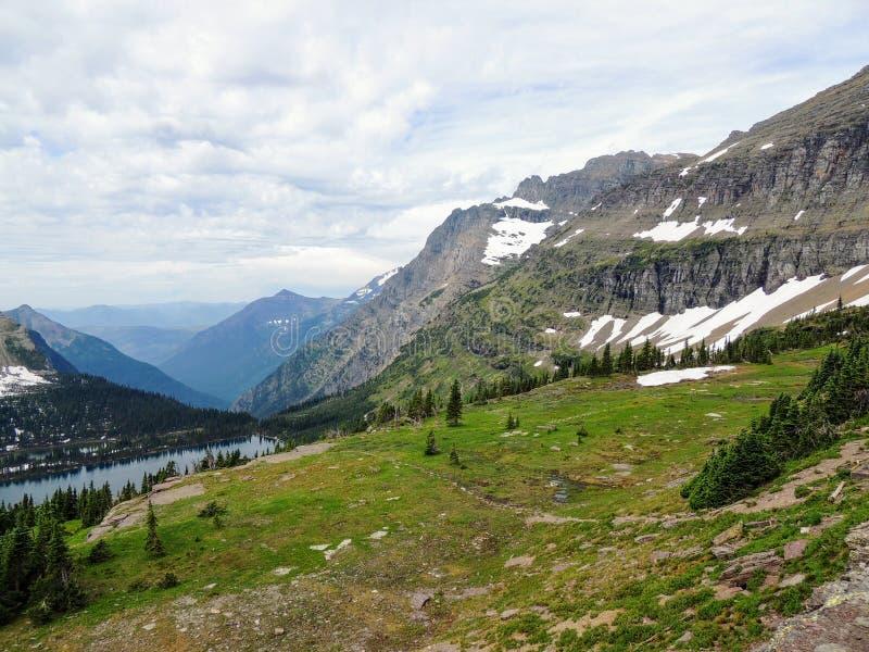 Yendo al camino de Sun, vista del paisaje, campos de nieve en Parque Nacional Glacier alrededor de Logan Pass, lago ocultado, ras imágenes de archivo libres de regalías