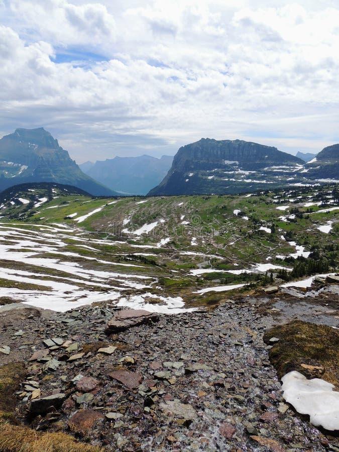 Yendo al camino de Sun, vista del paisaje, campos de nieve en Parque Nacional Glacier alrededor de Logan Pass, lago ocultado, ras imagenes de archivo